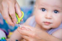 Nahaufnahmemutter-Ausschnittnagel des Babys mit Sicherheit scissors Mutterzutat-Kinderfingernägel Kindergesundheitswesen und Hygi lizenzfreie stockfotos