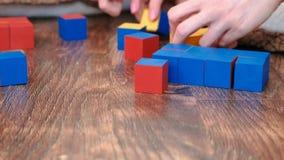 Nahaufnahmemutter und -sohn ` s übergibt den Aufbau einer ein-farbigen blauen Form von den Würfeln stock video