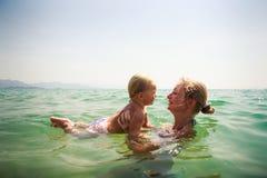 Nahaufnahmemutter unterrichtet Schwimmen kleine Tochter im azurblauen Meer Stockbild