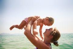 Nahaufnahmemutter unterrichtet Schwimmen kleine Tochter im azurblauen Meer Stockfotografie