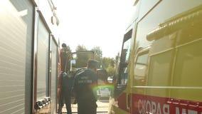 Nahaufnahmenotministeriumangestelltgespräch telefonisch nahe Krankenwagen stock video