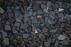 Nahaufnahmeoberfläche des zerquetschten Felsens der Tapetenbeschaffenheit schwarze stockfotos