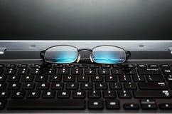 Nahaufnahmepaare Gläser auf der Laptoptastatur Stockbilder