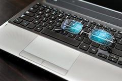Nahaufnahmepaare Gläser auf der Laptoptastatur Lizenzfreie Stockfotografie