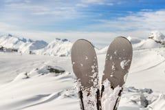 Nahaufnahmepaare Skis auf Gebirgswinterurlaubsort mit panoramischer szenischer Ansicht des Skiliftes und des sch?nen Winterberges stockbild