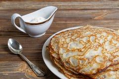 Nahaufnahmepfannkuchen auf dem Teller und dem Sauerrahm Lizenzfreie Stockfotos