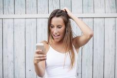 Nahaufnahmeporträt überraschte das junge Mädchen, welches das Telefon betrachtet, das Nachrichten oder Fotos sieht Stockfotografie