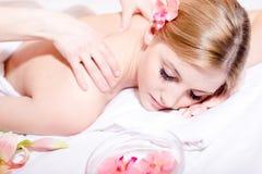Nahaufnahmeporträt auf der schönen jungen Frau, die Badekuren hat: Genießen von Massage, von Steinen u. von Aromatherapie Stockfotografie