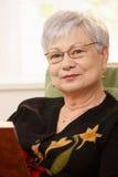 Nahaufnahmeporträt der älteren Frau mit Buch Stockbild