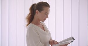 Nahaufnahmeporträt der älteren kaukasischen brunette Geschäftsfrau, die ein Buch betrachtet die Kamera steht in einem Weiß liest stock video footage