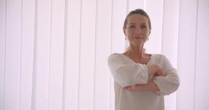 Nahaufnahmeporträt der älteren kaukasischen brunette Geschäftsfrau, welche die Kamera lässt ihre Arme über Kasten kreuzen betrach stock video