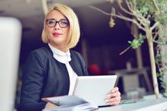 Nahaufnahmeporträt der aktiven Geschäftsfrau, die Laptop bei der Stellung im Büro hält Lizenzfreie Stockbilder