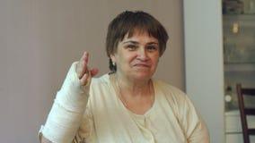 Nahaufnahmeporträt der alten Frau mit dem gebrochenen Arm, ihre Hand in einer Form stock footage