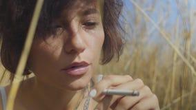 Nahaufnahmeporträt der attraktiven Frau mit der rauchenden Zigarette des kurzen Haares, die unter dem Weizenfeld weg schaut sitzt stock footage