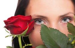 Nahaufnahmeporträt der attraktiven jungen Frau, die eine rote Rose anhält Stockbilder