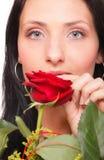 Nahaufnahmeporträt der attraktiven jungen Frau, die eine rote Rose anhält Lizenzfreies Stockfoto