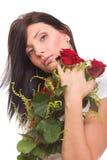 Nahaufnahmeporträt der attraktiven jungen Frau, die eine rote Rose anhält Lizenzfreie Stockfotos