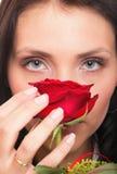Nahaufnahmeporträt der attraktiven jungen Frau, die eine rote Rose anhält Stockbild