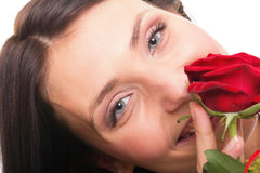 Nahaufnahmeporträt der attraktiven jungen Frau, die eine rote Rose anhält Lizenzfreie Stockfotografie