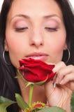 Nahaufnahmeporträt der attraktiven jungen Frau, die eine rote Rose hält Lizenzfreies Stockfoto