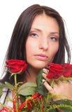 Nahaufnahmeporträt der attraktiven jungen Frau, die eine rote Rose hält Stockbilder