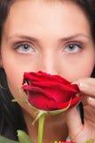 Nahaufnahmeporträt der attraktiven jungen Frau, die eine rote Rose hält Stockfotos