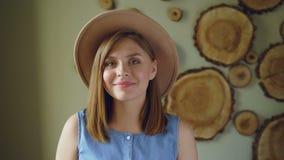 Nahaufnahmeporträt der attraktiven jungen Frau mit dem blonden Haar, welches die modische Hut- und Denimspitze betrachtet Kamera  stock video footage