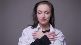 Nahaufnahmeporträt der erwachsenen attraktiven kaukasischen Frau, die im Vertrauen und ein Auge lächelt zu blinzeln lässt, Kamera stock footage