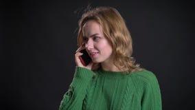 Nahaufnahmeporträt der erwachsenen kaukasischen einen Telefonanruf machenden und beim Lächeln sprechenden Frau vor der Kamera stock video footage