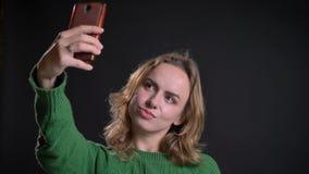 Nahaufnahmeporträt der erwachsenen kaukasischen Frau, die selfies am Telefon nimmt und ihr Haar repariert stock video