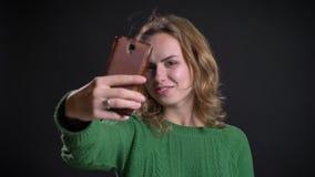 Nahaufnahmeporträt der erwachsenen kaukasischen Frau, die selfies am Telefon nimmt und verschiedene Gesichtsausdrücke macht stock video