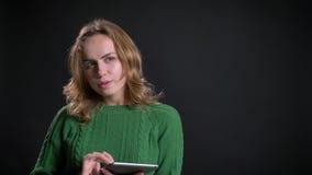 Nahaufnahmeporträt der erwachsenen kaukasischen Frau unter Verwendung der Tablette und des Seins durchdacht vor der Kamera stock video