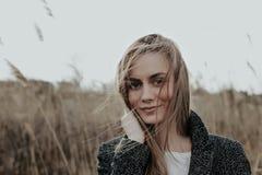 Nahaufnahmeporträt der Frau im Wintermantel, der Kamera auf Binsenhintergrund betrachtet Stockbild