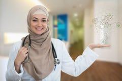 Nahaufnahmeporträt der freundlichen, lächelnden überzeugten moslemischen Ärztin, die Moleküle hält Lizenzfreie Stockfotos