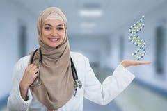Nahaufnahmeporträt der freundlichen, lächelnden überzeugten moslemischen Ärztin, die Moleküle hält Lizenzfreie Stockfotografie