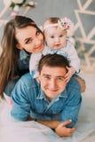 Nahaufnahmeporträt der glücklichen Familie Mutter umarmt das Baby, während sie auf den Schultern des Vaters sitzt stockfotografie
