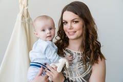 Nahaufnahmeporträt der glücklichen jungen Mutter, die sein süßes entzückendes Kind umarmt und küsst Schoss zuhause, Konzeptbild Lizenzfreie Stockbilder