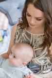Nahaufnahmeporträt der glücklichen jungen Mutter, die sein süßes entzückendes Kind umarmt und küsst Schoss zuhause, Konzeptbild Stockfoto