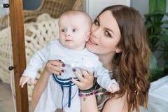 Nahaufnahmeporträt der glücklichen jungen Mutter, die sein süßes entzückendes Kind umarmt und küsst Schoss zuhause, Konzeptbild Lizenzfreies Stockbild