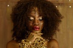 Nahaufnahmeporträt der jungen Afrikanerin mit Goldmake-up und -halskette, Hände auf ihr Kinn legend, das unten, brauner Hintergru lizenzfreie stockbilder