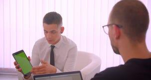 Nahaufnahmeporträt der jungen attraktiven Geschäftsmannvertretungstablette mit grünem Farbenreinheitsschirm zu seinem Partner unt stock video