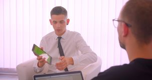 Nahaufnahmeporträt der jungen attraktiven Geschäftsmannvertretungstablette mit grünem Schirm zu seinem Partner unter Verwendung d stock video footage