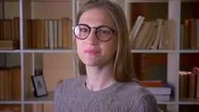 Nahaufnahmeporträt der jungen attraktiven Studentin in den Gläsern lächelnd und Kamera in der Collegebibliothek betrachtend stock video