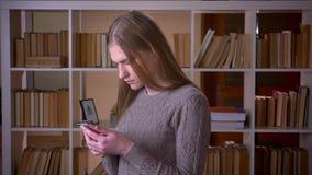 Nahaufnahmeporträt der jungen attraktiven Studentin, die das Telefon verwendet und zuhause Kamera in der Collegebibliothek betrac stock video