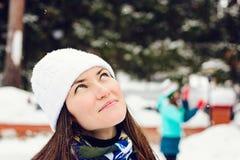 Nahaufnahmeporträt der jungen Frau im weißen Winterhut an der Eisbahn, an den Ständen und an den Träumen des Untersuchung den Him Stockfotografie