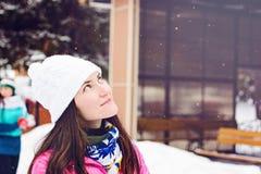 Nahaufnahmeporträt der jungen Frau im weißen Winterhut an der Eisbahn, an den Ständen und an den Träumen des Untersuchung den Him Lizenzfreie Stockfotografie