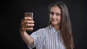 Nahaufnahmeporträt der jungen hübschen kaukasischen Frau, die selfies am Telefon nimmt und vor der Kamera mit lächelt stockbilder