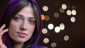 Nahaufnahmeporträt der jungen hübschen kaukasischen Frau in einem Hoodie lächelnd mit Charme und Kamera gerade betrachtend stock footage