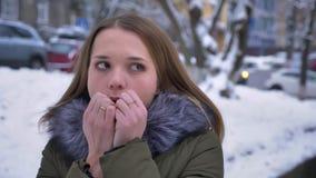 Nahaufnahmeporträt der jungen hübschen kaukasischen Frau mit dem brunette Haar, das kalt ist und ihre Hände an einem schneebedeck stock video footage