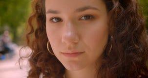 Nahaufnahmeporträt der jungen hübschen langhaarigen gelockten kaukasischen Frau, die draußen Kamera im Garten betrachtet stock video